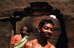 எரிந்து, பகுதி இடிந்து போன தன் வீட்டினுள்ளே கோவசி அத்மா உடன் அவரது மனைவி