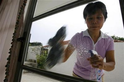 A maid cleans a window in Singapore November 3, 2006. REUTERS/Nicky Loh