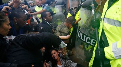 Protestors scuffle with police during a protest at the Ferguson Police Department in Ferguson, Missouri, October 13, 2014. Hundreds of protesters converged in the pouring rain on the Ferguson, Missouri, police department on Monday as they launched another day of demonstrations over the August killing by police of an unarmed black teenager. REUTERS/Jim Young (UNITED STATES - Tags: CRIME LAW CIVIL UNREST) - RTR4A14U